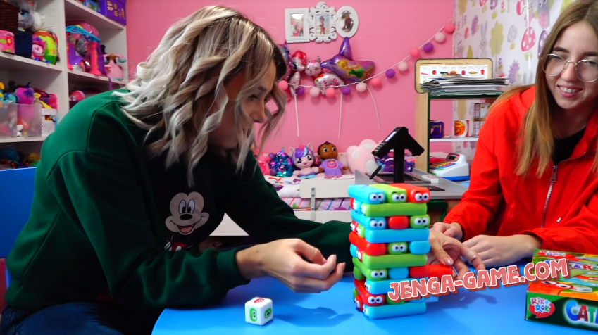 Girls play colored Jenga for kids